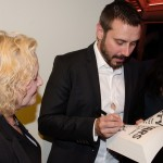 """jeremy signs a book for Stacey."""